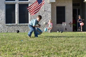 Current Easter stories; Children with Easter baskets hunting eggs in yard with American Flag in the background