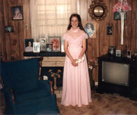 Machelle in the living room dressed up for Prom surrounded by framed pictures on the wall, faux fireplace & TV. Enjoy Your Photos